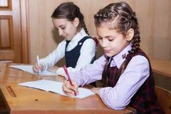 Uczennicy writing w sala lekcyjnej fotografia stock