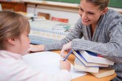 Uczennicy writing z jej uśmiechniętym nauczycielem Obrazy Royalty Free