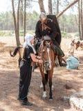 Uczestnicy w odbudowie rogi Hattin bitwa w 1187 jeden siedzą na batalistycznym koniu, i drugi jeden trzyma konia Fotografia Stock