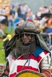 Uczestnik festiwal w knightly opancerzeniu ono uśmiecha się przed Obraz Stock