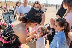 Uczestnik Purim festiwal ubierający w bajecznie kostiumu, stawia rysunek na dziewczyny ` s twarzy w Caesarea, Izrael Fotografia Stock