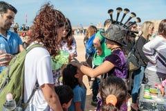 Uczestnik Purim festiwal ubierający w bajecznie kostiumu, stawia rysunek na dziewczyny ` s twarzy w Caesarea, Izrael Obraz Royalty Free