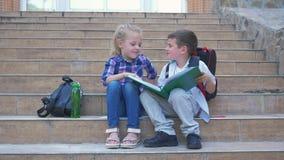Uczni dzieciaki czyta i leafing przez książkowego obsiadania na krokach szkoła w na wolnym powietrzu podczas recesji z plecakami