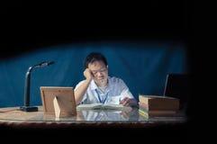 Ucznia spadać uśpiony podczas gdy studiujący przy biurkiem Biurowy pokój strzelający za szkłem Fotografia Stock
