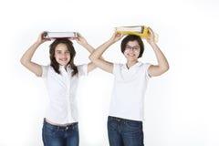 Ucznie balansują ciężkie książki na głowach obraz stock