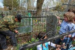 Ucznie dba dla grób zmarły dyrektor szkoły w Kaluga regionie Rosja Fotografia Stock