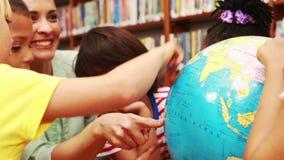 Ucznie i nauczyciel patrzeje kulę ziemską w bibliotece zbiory wideo
