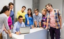 Ucznie i nauczyciel z laptopem przy szkołą obraz stock