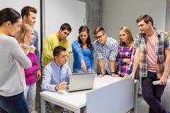 Ucznie i nauczyciel z laptopem przy szkołą zdjęcie royalty free
