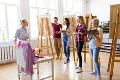 Ucznie i nauczyciel z spokojnym życiem przy szkołą artystyczną zdjęcia stock