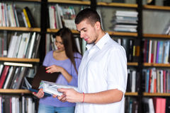 Ucznie komunikują w bibliotece młody człowiek i kobieta opowiada w bibliotece zdjęcie royalty free