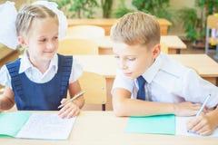 Ucznie lub kolega z klasy w szkolnej sala lekcyjnej siedzi wpólnie przy biurkiem fotografia royalty free