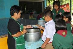 Ucznie otrzymywają jedzenie od kobieta kucharza Obrazy Stock