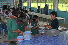 Ucznie otrzymywają jedzenie od kobieta kucharza Fotografia Royalty Free