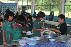 Ucznie otrzymywają jedzenie od kobieta kucharza Zdjęcia Stock