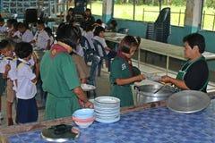 Ucznie otrzymywają jedzenie od kobieta kucharza Obraz Royalty Free