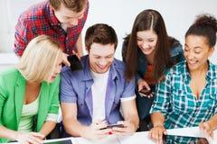 Ucznie patrzeje w smartphone przy szkołą Obrazy Stock