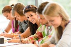 Ucznie pisze przy szkoły średniej egzaminu wiek dojrzewania nauką Fotografia Stock