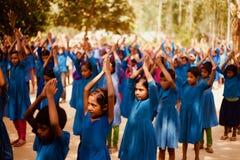 Ucznie podnosi ich ręki w szkolnym zgromadzenie fotografia royalty free