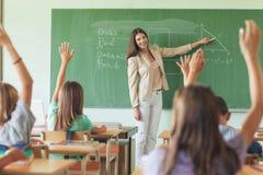 Ucznie Podnosi ręki w Maths Lekcyjni Zdjęcia Stock