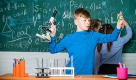 ucznie robi biologii eksperymentuj? z mikroskopem w lab Szcz??liwi dzieci Chemii lekcja Ma?ych dzieci uczy? si? fotografia stock