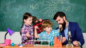 ucznie robi nauce eksperymentuj? z mikroskopem w lab szko?a ?artuje naukowa studiowania nauk? Szcz??liwi dzieci fotografia stock