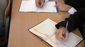 Ucznie siedzą przy biurka writing przydziałem od nauczyciela w dzienniczku zbiory wideo