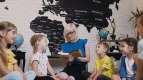 Ucznie siedzą w okręgu na podłoga na poduszkach gdy nauczyciel czyta one ciekawą książkę w klasie przy primare szkołą lub zbiory