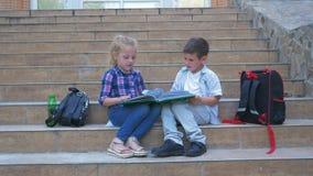 Ucznie siedzi na szkolnych krokach obok plecaków i leafing przez książki podczas recesji w na wolnym powietrzu