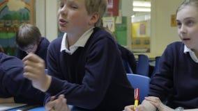 Ucznie Siedzi Przy biurkami Odpowiada pytania Od nauczyciela zdjęcie wideo