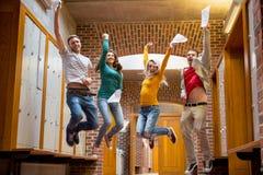 Ucznie skacze w szkoła wyższa korytarzu obrazy royalty free