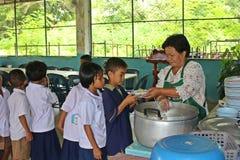 Ucznie stoją w rzędzie i otrzymywają jedzenie od kobieta kucharza Obraz Stock