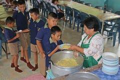 Ucznie stoją w rzędzie i otrzymywają jedzenie od kobieta kucharza Obraz Royalty Free