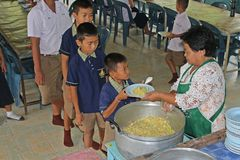 Ucznie stoją w rzędzie i otrzymywają jedzenie od kobieta kucharza Zdjęcia Royalty Free