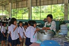 Ucznie stoją w rzędzie i otrzymywają jedzenie od kobieta kucharza Obrazy Stock
