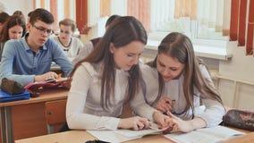 Ucznie studiują w sala lekcyjnej przy szkolnym biurkiem zbiory