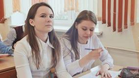 Ucznie studiują w sala lekcyjnej przy szkolnym biurkiem zdjęcie wideo