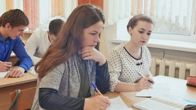 Ucznie studiują w sala lekcyjnej przy szkolnym biurkiem zbiory wideo