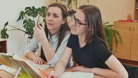 Ucznie studiują w sala lekcyjnej przy szkolnym biurkiem