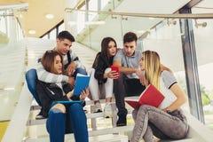 Ucznie studiuj? w bibliotece M?odzi ludzie wydaj? czas wp?lnie Czytelnicza ksi??ka i komunikowa? podczas gdy obrazy royalty free