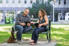 Ucznie Używa Cyfrowej pastylkę Na ławce Przy kampusem Obraz Royalty Free