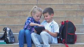 Ucznie używają cyfrowego pastylki obsiadanie na krokach z plecakami podczas recesji w na wolnym powietrzu