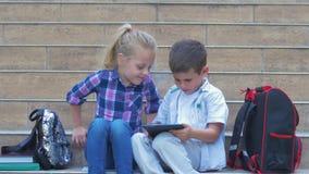 Ucznie używają cyfrowego pastylki obsiadanie na szkolnych krokach z plecakami w na wolnym powietrzu podczas przerwy