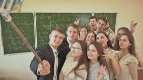 Ucznie w sala lekcyjnej amusingly robią selfie na tle zarząd szkoły zdjęcie wideo