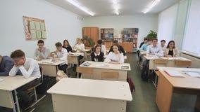 Ucznie w sala lekcyjnej siedzą przy szkolnymi biurkami przed lekcją Rosjanin szkoła zbiory