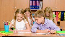 Uczniowski cyganienie przy egzaminem, patrzeje przyjaciela writing Zdjęcia Royalty Free