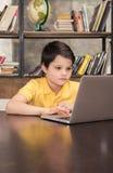 Uczniowski obsiadanie przy stołowym i używa laptopem obraz royalty free