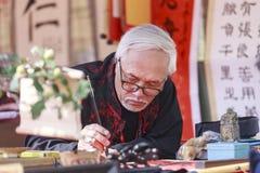 Uczony pisze Chińskich kaligrafia charaktery przy świątynią literatura obraz royalty free