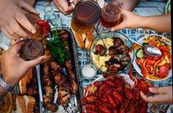 Uczta piwo, mięsny rakowy i skewer Odgórny widok na grupie ludzi który je obiad outdoors Obraz Royalty Free