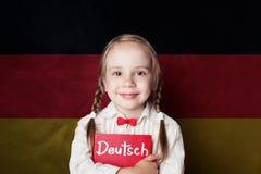 Uczyć się niemieckiego języka pojęcie z szczęśliwą dziecko dziewczyną fotografia stock